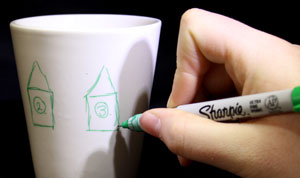 White mug with green houses drawn on it.
