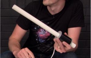 Hand holding a ring launcher that looks like a rod with a handle