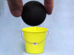 A person holding a squash ball. In the background, there is a bucket. The bucket and the ball appear the same width.