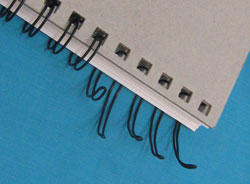 The spine of a spiral bound notebook. Some of the wire has been bent so it no longer holds the pages together.
