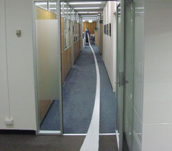 A long corridor. Someone is unrolling toilet paper all the way along the corridor.