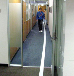 Toilet paper unrolled down a long corridor. Someone is walking back along the corridor, holding the end of the toilet paper.