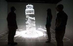 Three people looking at a 3D map of the Leaning Tower of Pisa.
