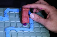 A rectangle of plasticine on a square grid board. someone is rolling the rectangle up onto its end, and the square it is rolling onto is marked.