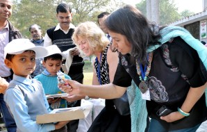 Dr Anu Kumar giving a child an Australian souvenir.