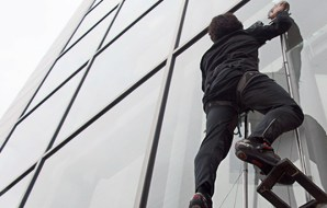 A person wearing gloves and a harness climbing stright up a glass wall.