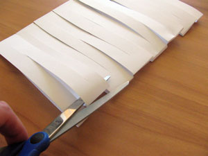 Someoen is cutting along the fold of the sheet of paper.