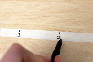 Someone is writing numbers on a strip of masking tape.