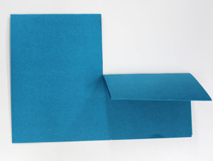 A piece of paper, folded in half, and with a cut to the middle. One side of the cut is folded up.