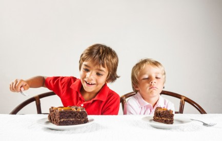 Two kids, one with a big slice of cake and one with a smaller slice.