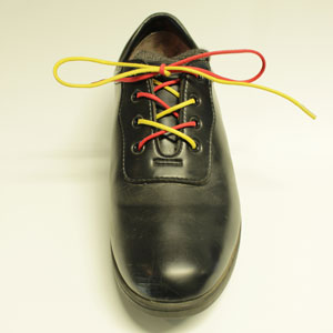 A shoe with red and yellow laces, and a nice straight bow.