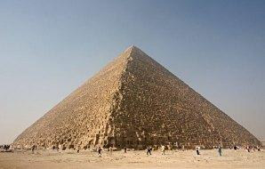Image of a pyramid with tiny people in the foreground.