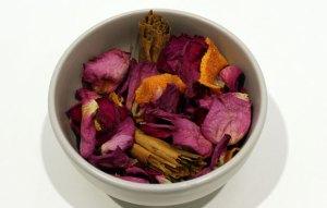 A bowl filled with dried rose petals, orange peel and cinnamon sticks
