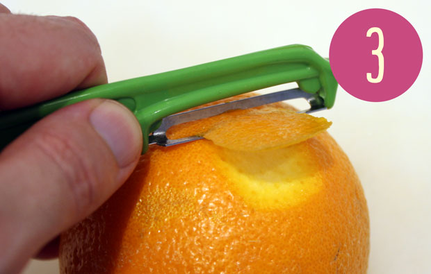 someone peeling an orange with a vegetable peeler