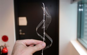 A piece of string, knotted at regular intervals, being held srtaight by three plastic strips which attach to the knots in the string.