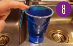 Cup of blue liquid with a straw bent over the rim of the cup and blue liquid pouring out.
