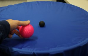 A hand placing a larger pink ball onto a piece of blue fabric which already has a small black ball on it.
