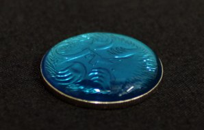 A five cent coin with a convex drop of blue water covering the surface.
