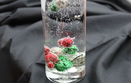 Small metal bells in a glass of fizzy water