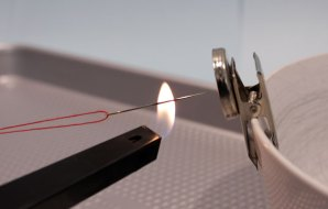 Flame heating a needle held in place by a magnet.