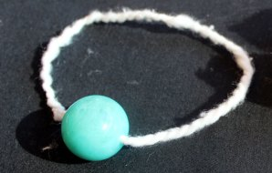 A green bead the size of a marble threaded onto a piece of string.