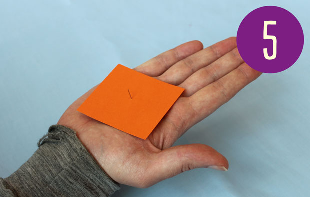 Holding a square of orange card with a pin sticking through the centre.