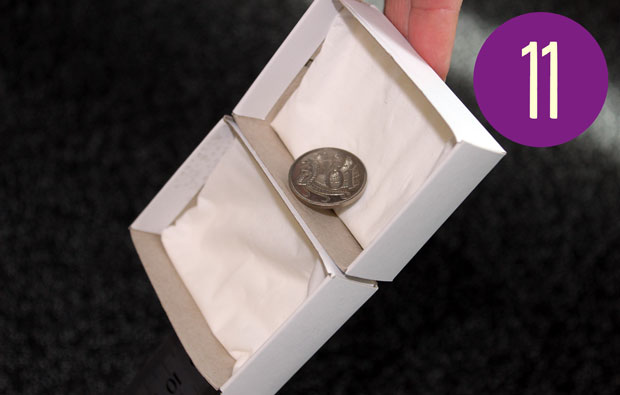 Ten cent coin in the higher of two matchbox drawers, side by side.
