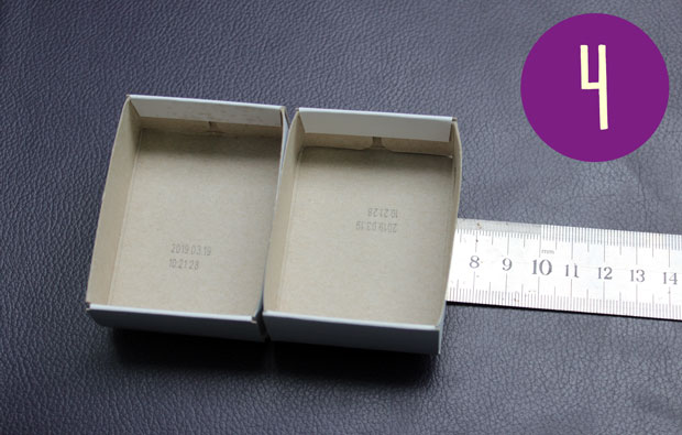 Two matchbox drawers on a ruler.