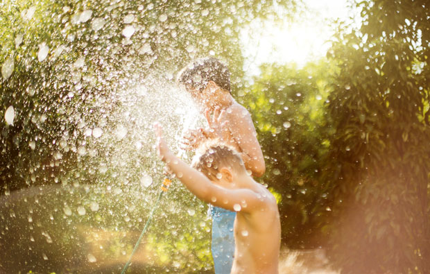 Two boys playing with a hose