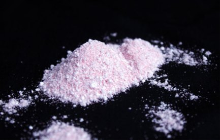Small pile of pink powder on a black surface.