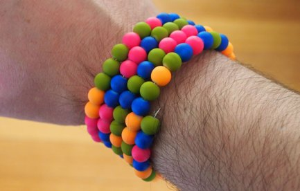 Colourful beaded bracelet worn on an arm.