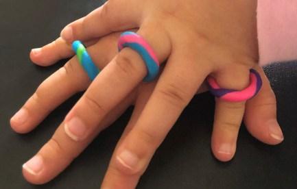 A child's hand ontop of a larger hand, both hands are wearing colourful rings