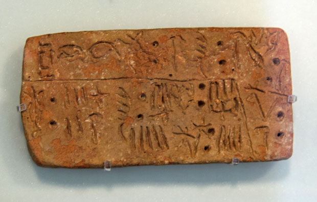 Clay tablet with scratched marks on it.