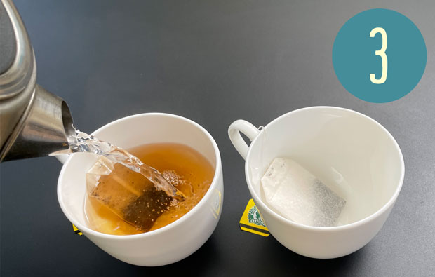 Someone is pouring water into a teacup with a teabag in it
