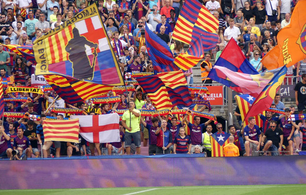 Crowd of football fans waving flags from the stands.