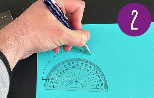 Using a protractor to draw a curve onto the card.