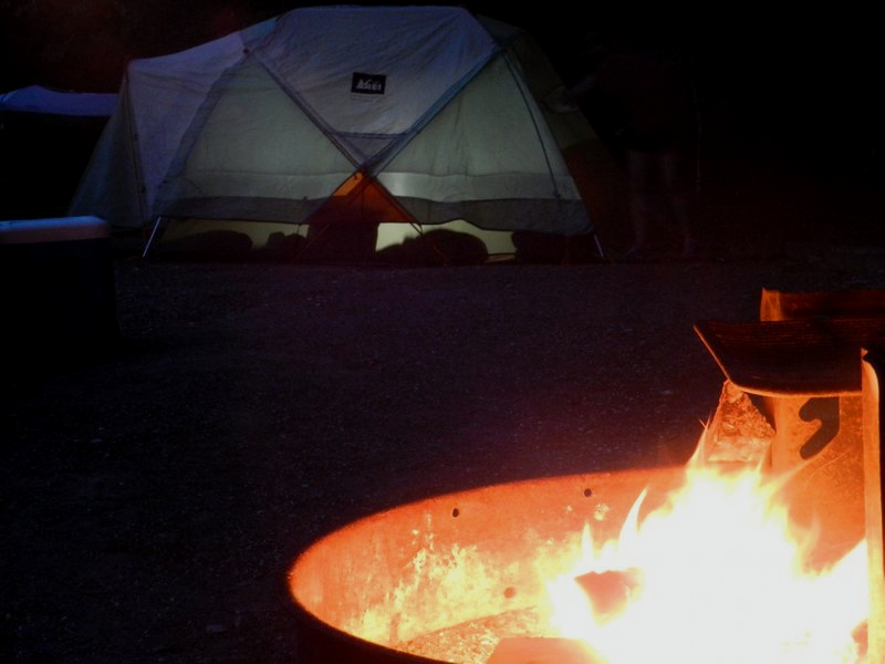 Photograph of a campfire with a tent in the background