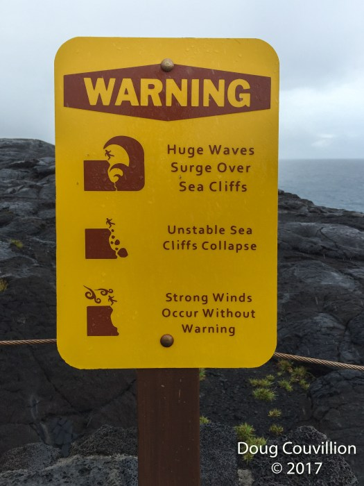 photo of a sign warning of huge wave, unstable cliffs and strong winds