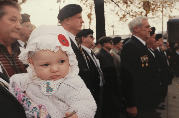 close up of a baby being held during a remembrance day ceremony, with a poppy stuck to her hat