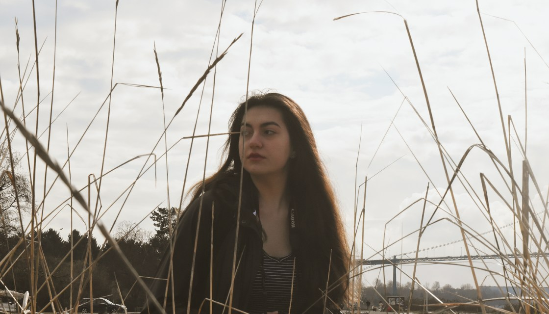 Malena, refugee to Canada, basketball scholarship student to Douglas, sits on a beach with tall grass in front and a bridge behind her