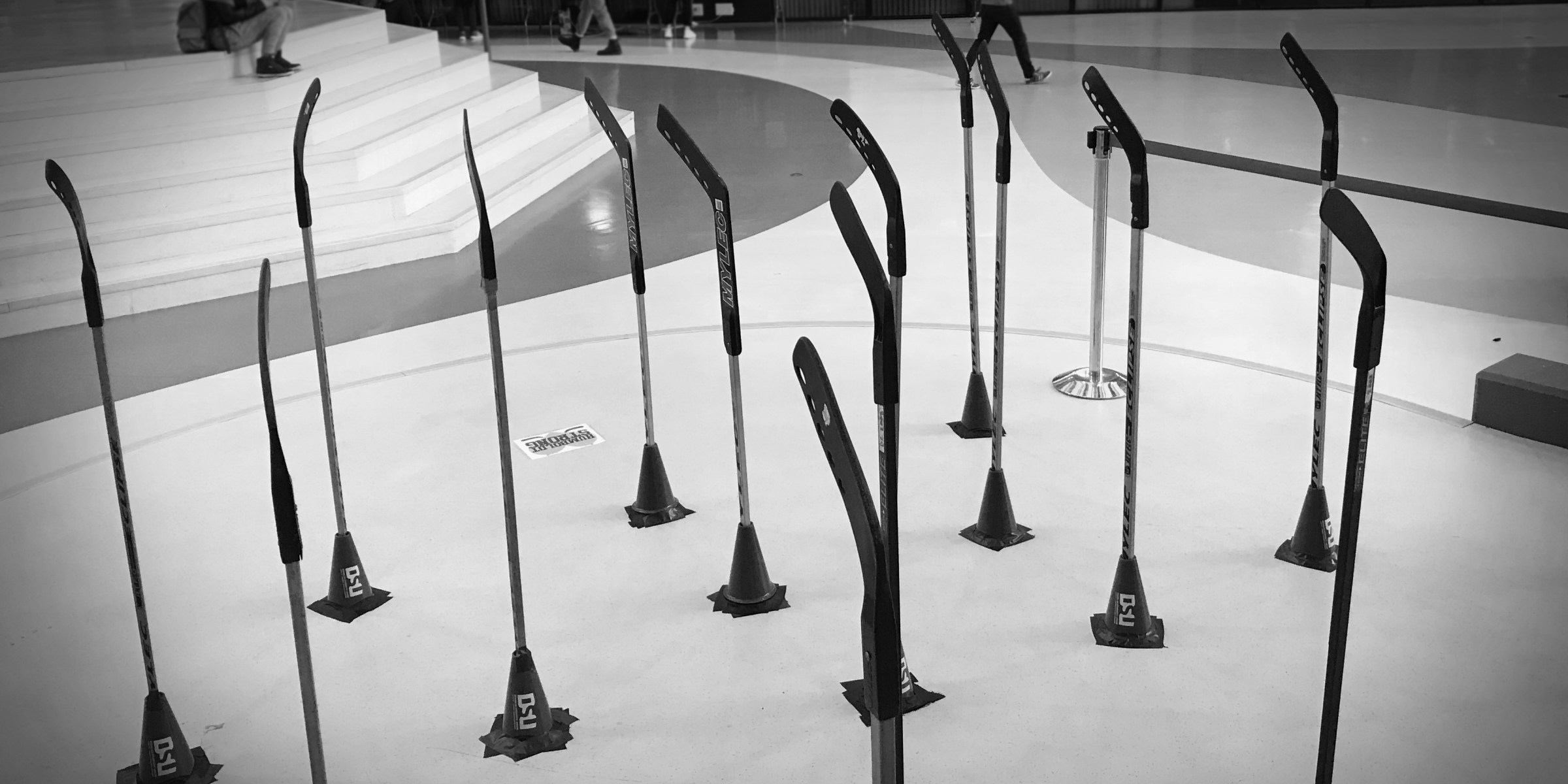 16 Hockey sticks standing upright in the concourse in tribute to Humboldt