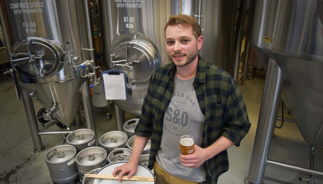 Douglas Music alum Jay Schreiber stands in Steel & Oak brewing room with drum and glass of beer