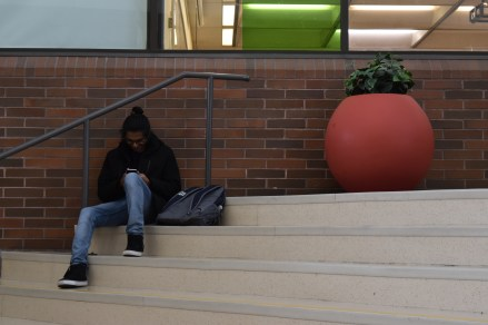 A student checks their phone in the New Westminster concourse.