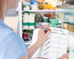 Person creating a meal plan for the week in front of an open refrigerator