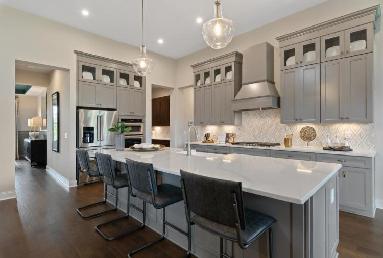 A gourmet kitchen featuring gray cabinets and a large serving island