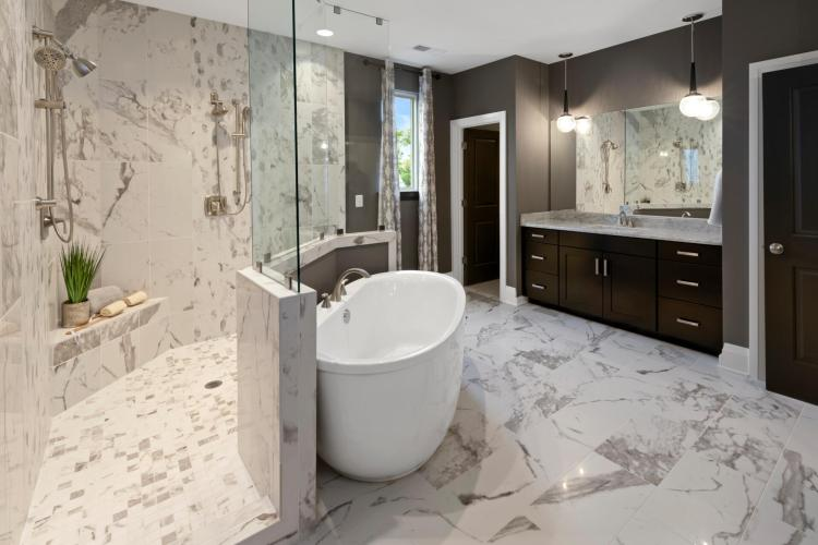 Luxurious owner's suite bathroom featuring an enormous walk-in, super shower and free-standing tub by Drees Homes in Washington D.C.