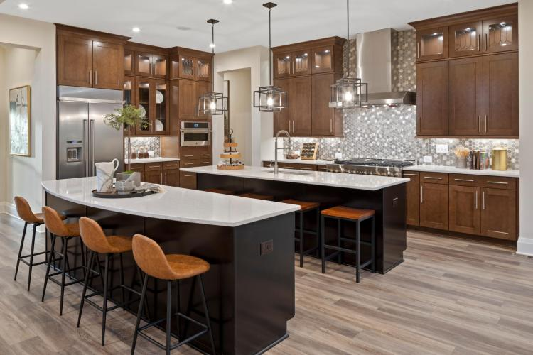 The Great Falls kitchen featuring warm wood cabinets and two enormous serving islands by Drees Homes in Washington D.C.