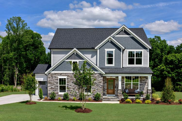 two story home with stone, shakes, siding and a three-car garage