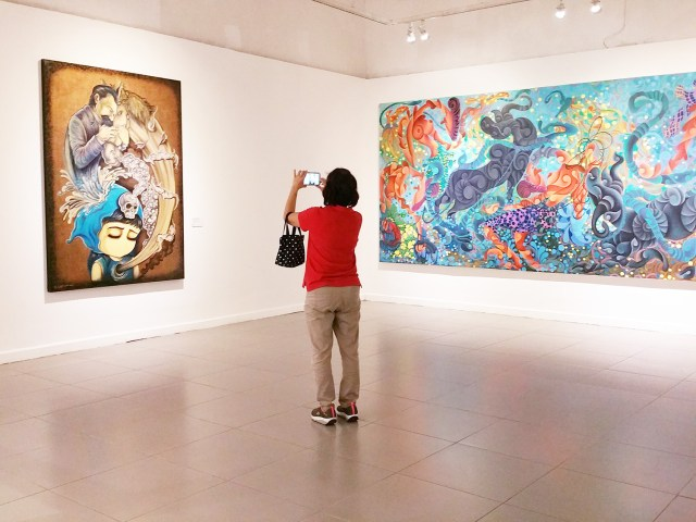 A visitor taking photos of Andre Tanama's emo painting
