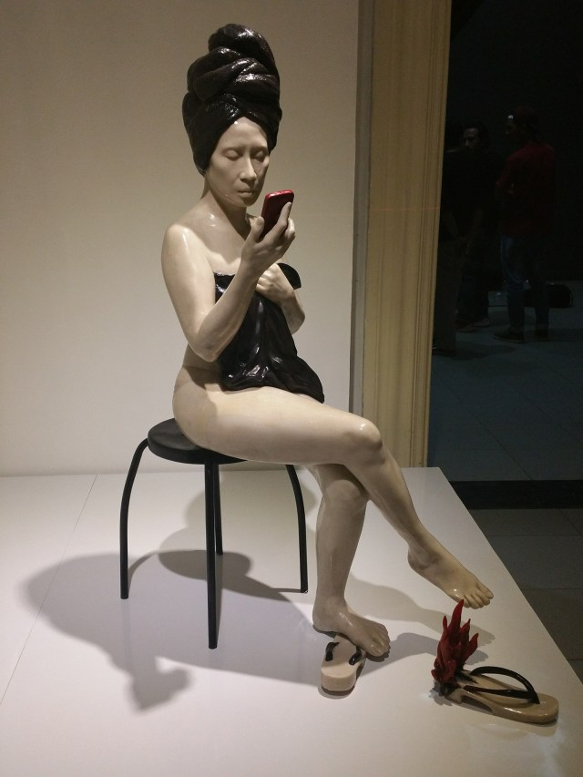 Julie Lluch's naked girl looking at phone in bathroom sculpture. One of her slippers are on fire too